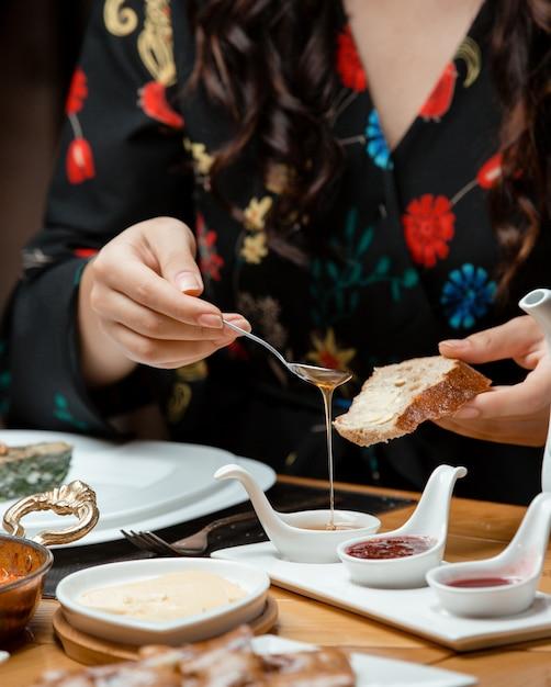 La donna mette il miele sul suo pane nella tradizionale colazione Foto Gratuite
