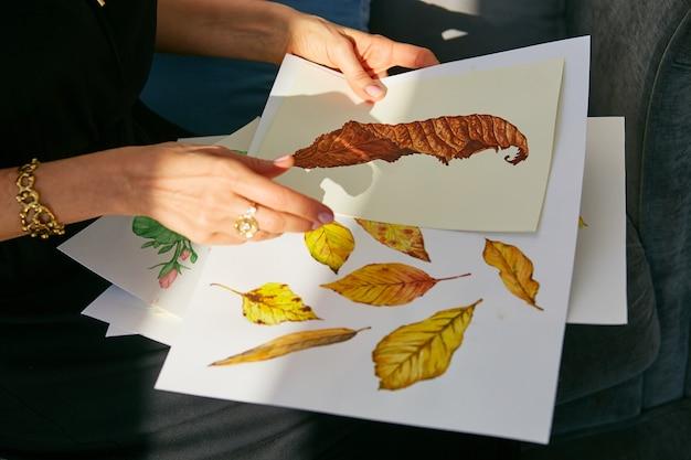 La donna osserva attraverso illustrazioni acriliche con foglie d'autunno Foto Gratuite