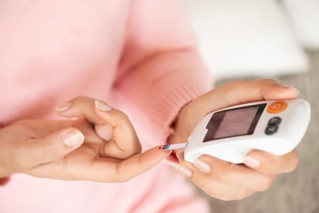 La donna passa il controllo del livello di zucchero nel sangue dal glucometro per il tester del diabete Foto Premium
