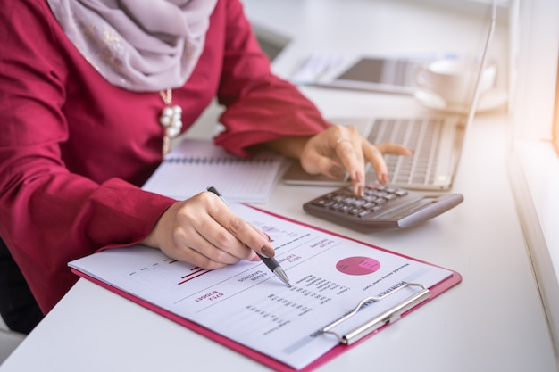 La donna passa il lavoro con il calcolatore circa la pianificazione finanziaria personale al caffè. Foto Premium