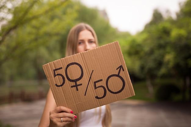 La donna passa la tenuta del cartello con il simbolo maschio e femminile Foto Premium