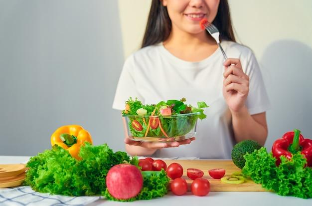 La donna passa la tenuta dell'insalatiera con il cibo del pomodoro e le varie verdure a foglia verde sulla tavola a casa. Foto Premium