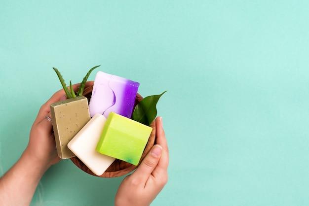 La donna passa la tenuta della barra di sapone naturale naturale di colore sul blu. concetto zero rifiuti domestici. Foto Premium