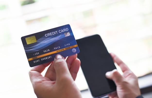 La donna passa la tenuta della carta di credito e lo smartphone usando per lo shopping online / la gente che paga il pagamento online del portafoglio dei soldi della tecnologia a casa Foto Premium