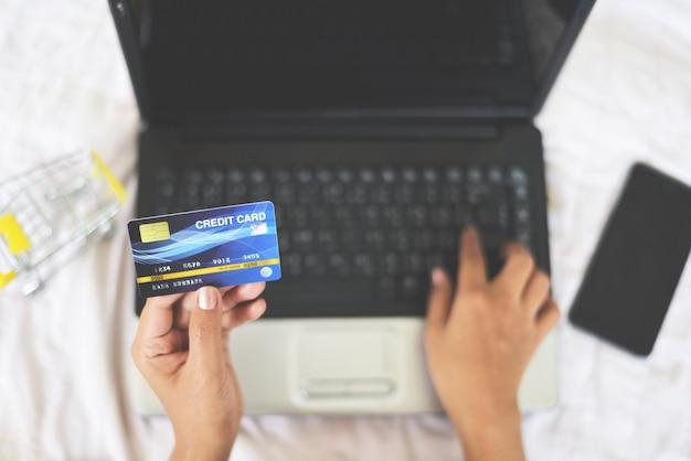 La donna passa la tenuta della carta di credito e per mezzo del computer portatile per l'acquisto online con il carrello Foto Premium