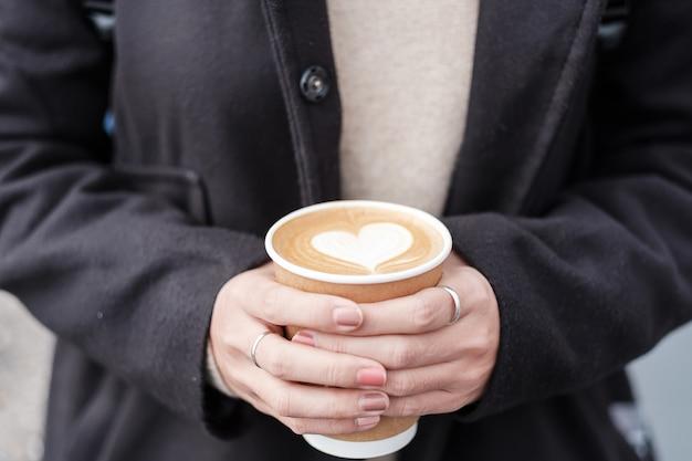 La donna passa la tenuta della tazza di carta del caffè caldo, l'arte del caffè del latte di forma del cuore. amore, vacanze, san valentino e concetto di contenitore di plastica gratuito Foto Premium