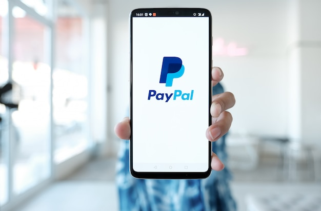 La donna passa lo smartphone della tenuta con le app di paypal sullo schermo. paypal è un sistema di pagamento elettronico online. Foto Premium