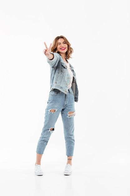La donna piacevole integrale in vestiti del denim fa l'occhiolino e mostrando il gesto di pace sopra la parete bianca Foto Gratuite