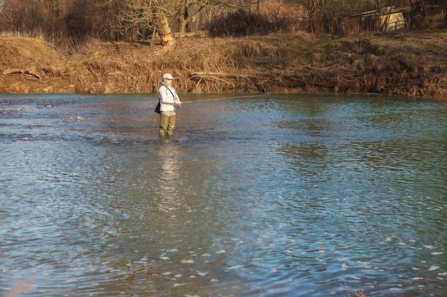 La donna prende il pesce di filatura che sta in un fiume Foto Premium