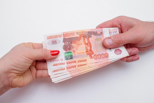La donna prende soldi dalle mani dell'uomo. scambio di denaro Foto Premium