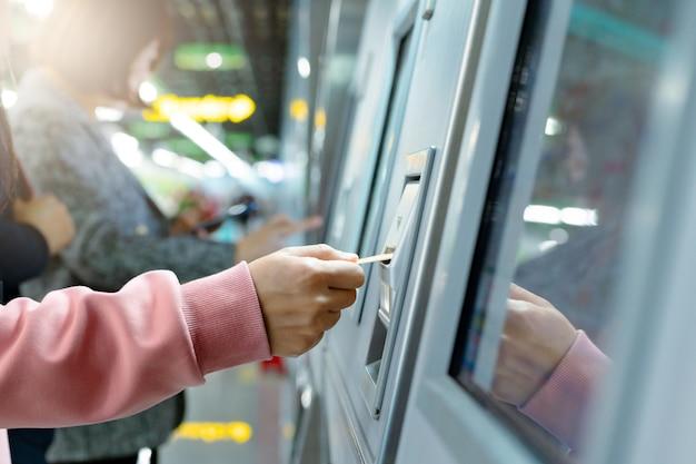 La donna prende un biglietto del treno dopo l'acquisto dal distributore di biglietti della metropolitana. concetto di trasporto Foto Premium