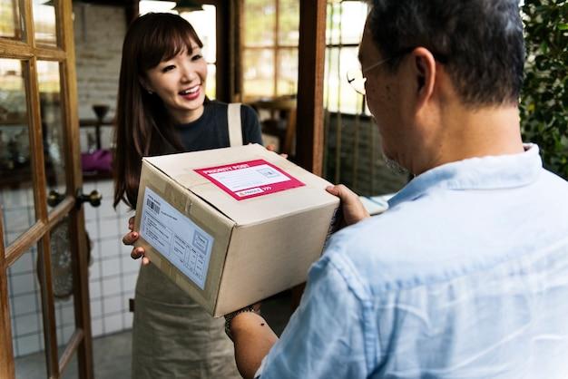La donna riceve una scatola consegnata a lei Foto Premium