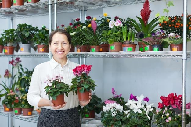 La donna sceglie cyclamen al negozio di fiori Foto Gratuite