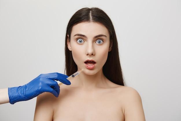 La donna scioccata apre la bocca e guarda preoccupata mentre prende l'iniezione di bottox nel labbro Foto Gratuite