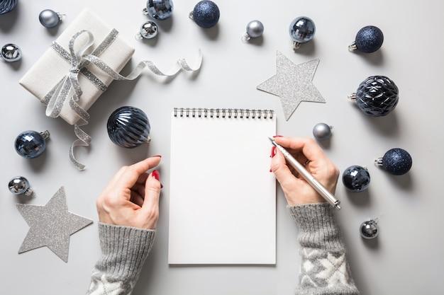 La donna scrive obiettivi, lista di controllo, piani e sogni per il nuovo anno. Foto Premium