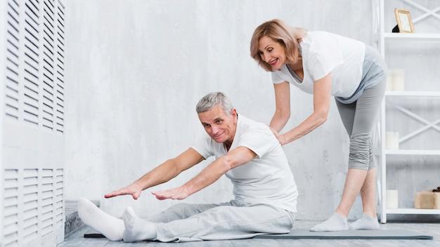 La donna senior felice a casa che aiuta i pensionati si accoppia per prendere la posizione corretta Foto Gratuite