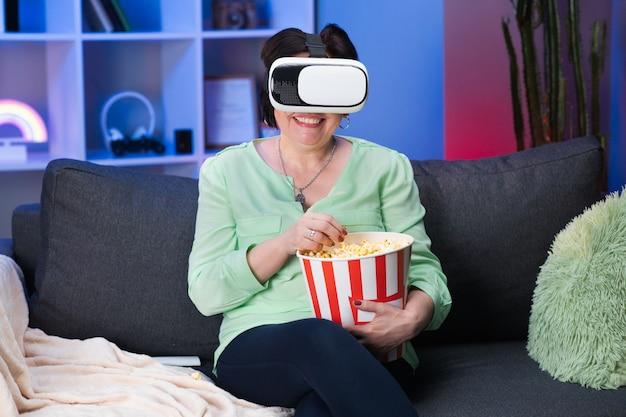 La donna senior indossa la cuffia avricolare di vr e tocca lo schermo virtuale alla notte. cuffia avricolare matura felice di realtà virtuale di usura della donna a casa. Foto Premium