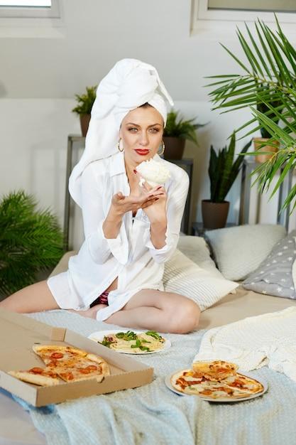 La donna senza complessi mangia la pizza e gli spaghetti a casa. gioia e risate sul volto della donna Foto Premium