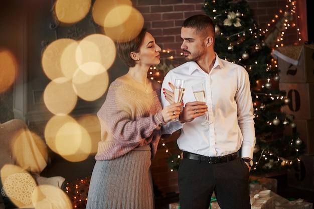 La donna si aggrappa a suo marito. belle coppie che celebrano il nuovo anno davanti all'albero di natale Foto Premium