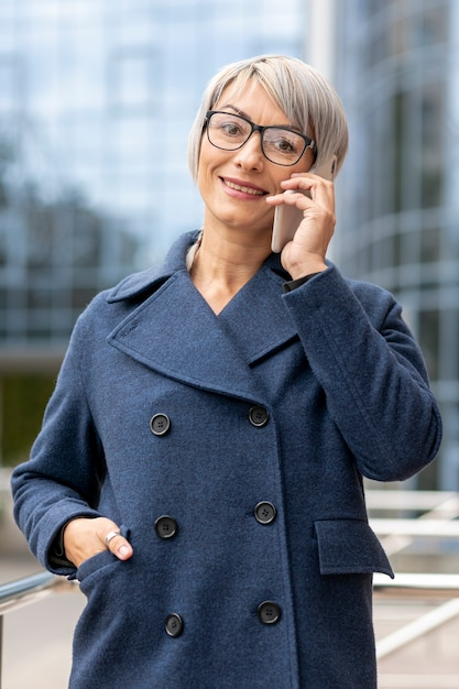La donna si è vestita in vestito che parla sopra il telefono Foto Gratuite