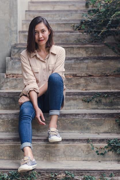 La donna si sedette sulla vecchia scala con piacere. Foto Premium