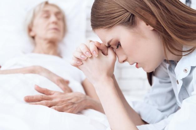 La donna si sente male, la ragazza sta pregando Foto Premium