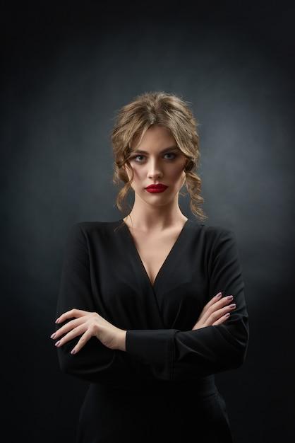 La donna sicura che indossa il rossetto rosso ed il vestito nero alla moda sta posando davanti alla macchina fotografica su fondo grigio scuro Foto Premium