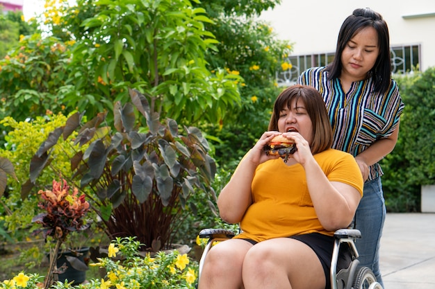 La donna sovrappeso è su una sedia a rotelle e mangia un hamburger. Foto Premium