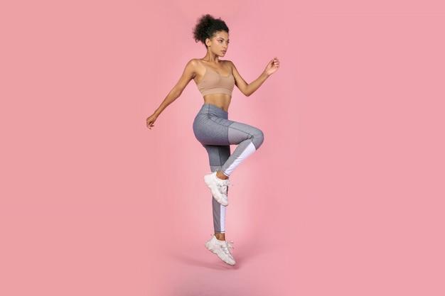 La donna sportiva che pratica lo squat si esercita in studio. donna africana in abiti sportivi che risolve su sfondo rosa. Foto Gratuite