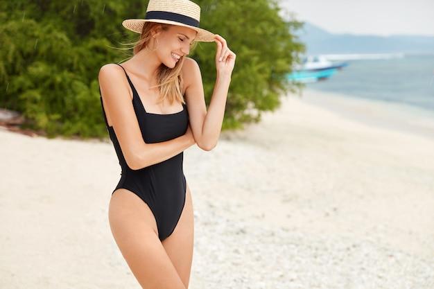 La donna sportiva in forma si trova sulla spiaggia tropicale, indossa un cappello e un costume da bagno estivi, si rilassa in riva all'oceano, respira aria fresca, guarda in basso con espressione felice, essendo un modello fotografico professionale. natura e relax Foto Gratuite
