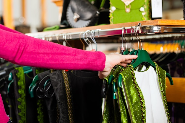 La donna sta acquistando tracht o dirndl in un negozio Foto Premium