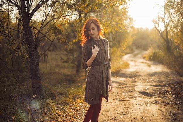 La donna sta camminando nel parco al tramonto Foto Premium