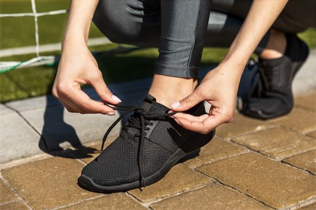La donna sta legando le scarpe da ginnastica estive vicino alle porte di calcio Foto Gratuite