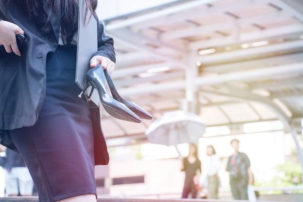 La donna sta portando scarpe nere a tacco alto. lei sta soffrendo. Foto Premium
