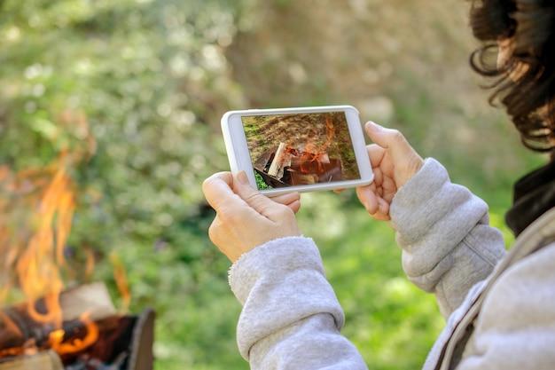 La donna sta scattando foto del fuoco sul suo smartphone. all'aperto. Foto Premium