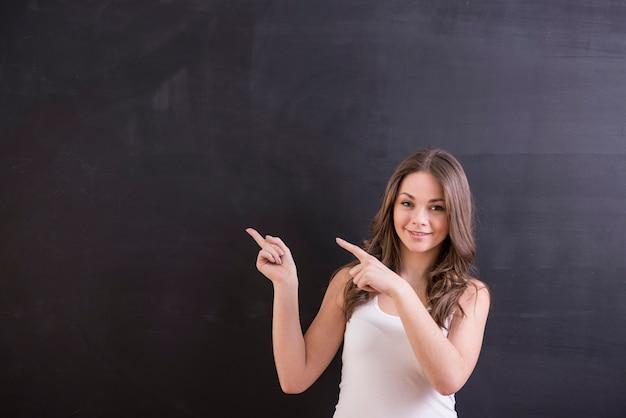 La donna sta stando davanti alla lavagna e indica su esso. Foto Premium