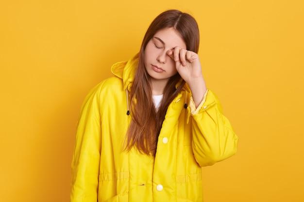 La donna stanca che indossa la giacca gialla si strofina l'occhio, femmina con bei capelli lunghi che posano con gli occhi chiusi, sembra esausta, in piedi contro il muro luminoso. Foto Gratuite