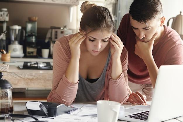 La donna stressata non sopporta la tensione della crisi finanziaria, stringendo le tempie, seduto al tavolo della cucina con una pila di banconote, laptop e calcolatrice. suo marito accanto a lei cerca di trovare una soluzione Foto Gratuite