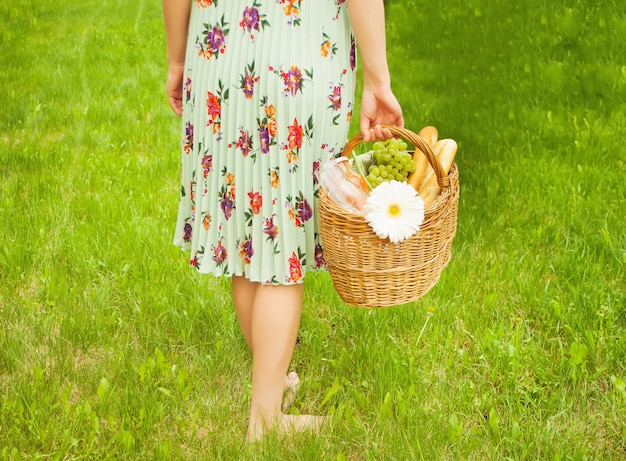 La donna sul picnic si leva in piedi sull'erba verde e tiene il cestino di picnic in una mano. Foto Premium