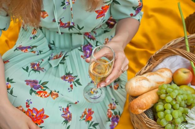 La donna sul picnic si siede sulla copertina gialla e tiene il bicchiere di vino. Foto Premium