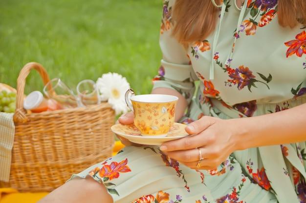 La donna sul picnic si siede sulla copertina gialla e tiene una tazza di tè o caffè. Foto Premium