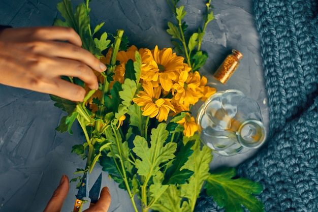 La donna taglia i fiori gialli del crisantemo per un vaso su un tavolo da loft antico Foto Premium