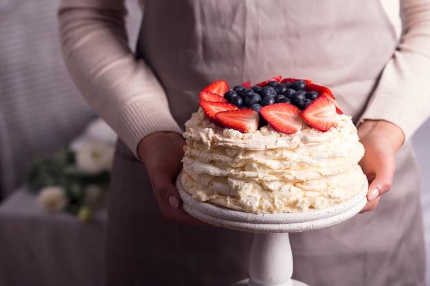 La donna tiene in mano il famoso dolce pavlova alla fragola Foto Premium