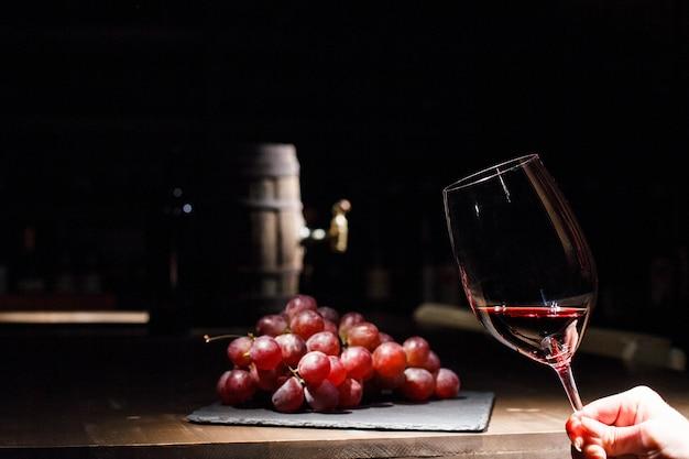 La donna tiene un bicchiere di vino prima di un grappolo d'uva che si trova sulla piastra nera Foto Gratuite