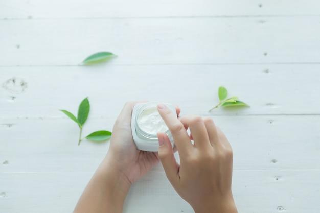 La donna tiene un vaso con una crema cosmetica nelle sue mani Foto Gratuite