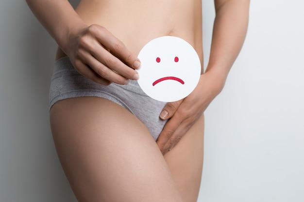 La donna tiene una faccia triste con doloroso periodo mestruale Foto Premium