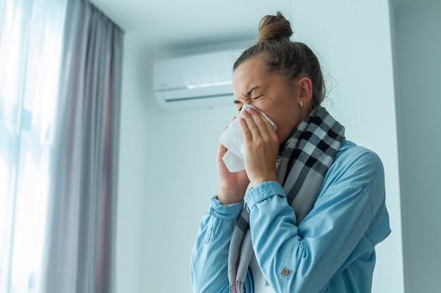La donna turbata ha preso un raffreddore dal condizionatore d'aria e starnutiva Foto Premium