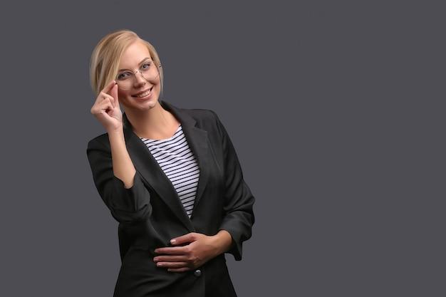 La donna, un'insegnante in giacca e occhiali su uno sfondo grigio, esprime emozioni. copyspace. Foto Premium
