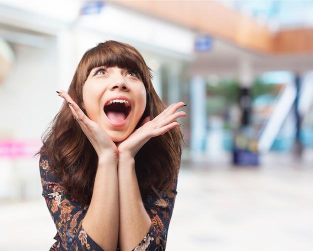 La donna urla con le mani sul mento Foto Gratuite