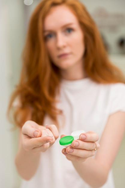 La donna vaga che mostra la lente a contatto con è contenitore Foto Gratuite